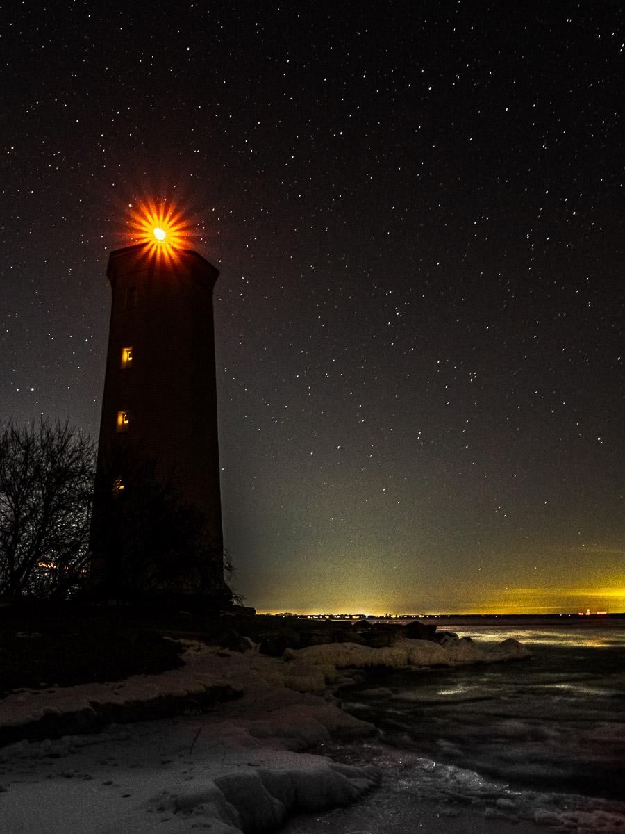 Presqu'ile Lighthouse at night along the shore ice